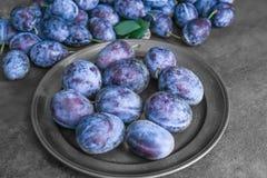 Plat avec les prunes mûres savoureuses Photo stock