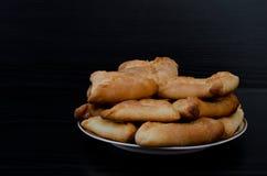 Plat avec les tartes parfumés frais sur une table en bois noire, déjeuner, echpochmak Copiez l'espace Photos stock