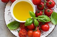 Plat avec les tomates-cerises, l'huile d'olive et le basilic Images libres de droits