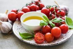 Plat avec les tomates-cerises, l'huile d'olive et le basilic Photos stock