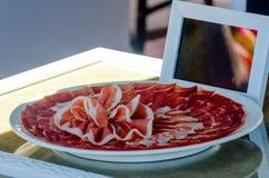 Plat avec les tranches coupées de serrano de jamon, jambon espagnol traditionnel Photos libres de droits