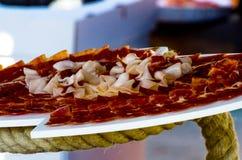 Plat avec les tranches coupées de serrano de jamon, jambon espagnol traditionnel Image stock