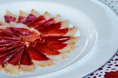 Plat avec les tranches coupées de serrano de jamon, jambon espagnol traditionnel Images stock