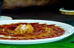 Plat avec les tranches coupées de serrano de jamon, jambon espagnol traditionnel Photo stock