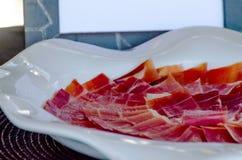 Plat avec les tranches coupées de serrano de jamon, jambon espagnol traditionnel Image libre de droits