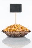 Plat avec un groupe de grains de maïs et sa réflexion et prix à payer, indicateur photos libres de droits