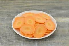 Plat blanc avec des carottes de tranches épaisses sur la table en bois Photo stock