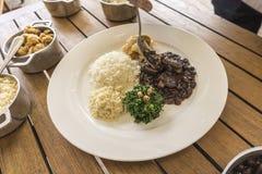 Plat blanc avec des ingrédients du feijoada, nourriture typique du Brésil photographie stock