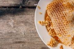 Plat blanc avec la section du nid d'abeilles de cire de la ruche sur le vi Photos stock