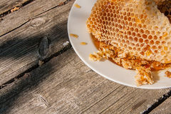 Plat blanc avec la section du nid d'abeilles de cire de la ruche sur le vi Photographie stock