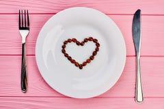 Plat blanc avec le coeur fait de grains de café Photo libre de droits