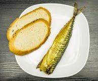 Plat blanc avec le maquereau fumé avec une peau d'or et des tranches de pain Photo libre de droits