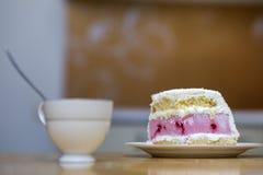 Plat blanc avec le morceau fait maison délicieux délicieux frais de gâteau crémeux blanc et rose de biscuit de fruit sur la table image libre de droits
