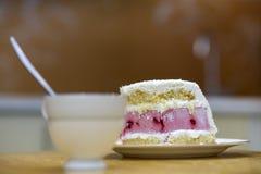 Plat blanc avec le morceau fait maison délicieux délicieux frais de gâteau crémeux blanc et rose de biscuit de fruit sur la table images stock