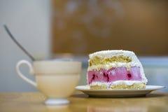 Plat blanc avec le morceau fait maison délicieux délicieux frais de gâteau crémeux blanc et rose de biscuit de fruit sur la table photographie stock libre de droits