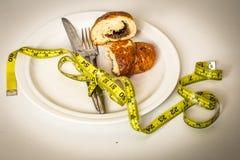 plat blanc avec le petit pain, le ruban métrique jaune et les couverts sur le fond Image libre de droits