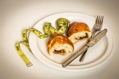 plat blanc avec le petit pain, le ruban métrique jaune et les couverts sur le fond Photo stock