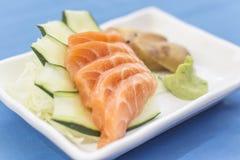 Plat blanc avec le sashimi saumoné sur le fond bleu images stock