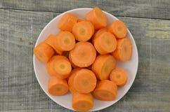 Plat blanc avec les carottes coupées profondément sur le fond en bois images stock