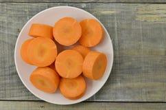Plat blanc avec les carottes coupées profondément sur le fond en bois photos libres de droits
