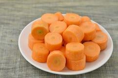 Plat blanc avec les carottes coupées profondément sur le fond en bois photos stock