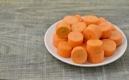 Plat blanc avec les carottes coupées profondément sur le fond en bois photographie stock libre de droits