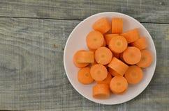 Plat blanc avec les carottes coupées profondément sur le fond en bois image libre de droits