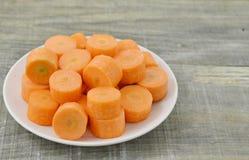 Plat blanc avec les carottes coupées profondément sur le fond en bois photo stock