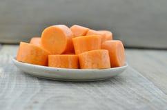 Plat blanc avec les carottes coupées profondément sur le fond en bois images libres de droits