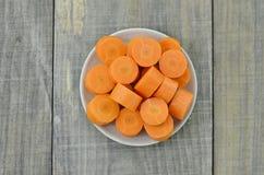 Plat blanc avec les carottes coupées profondément sur le fond en bois photo libre de droits