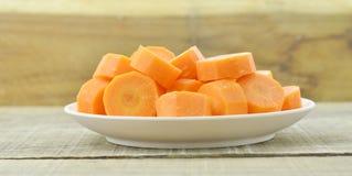 Plat blanc avec les carottes coupées profondément sur le fond en bois image stock