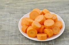 Plat blanc avec les carottes coupées profondément sur le fond en bois photographie stock