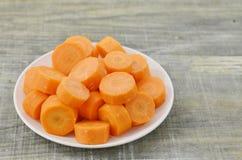 Plat blanc avec les carottes fraîches de coupe profondément sur le fond en bois photos libres de droits
