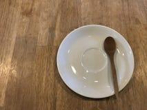 Plat blanc de dessert vide avec la cuillère en bois sur la table en bois brune naturelle Photographie stock libre de droits
