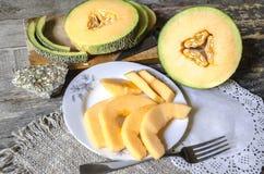 Plat blanc des tranches de melon Image libre de droits