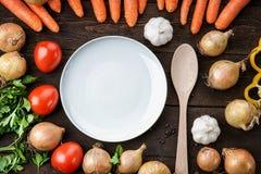 Plat blanc et cuillère en bois avec des légumes sur la table Images libres de droits