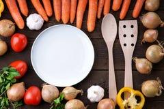 Plat blanc et vaisselle de cuisine en bois avec des légumes sur la table Photos libres de droits