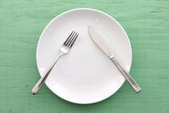 Plat blanc sur la table verte avec la PAUSE de signification de couverts image stock