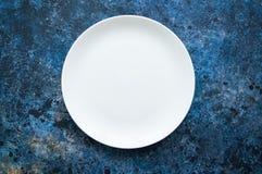 Plat blanc vide rond sur un fond texturisé bleu Vue supérieure Photo libre de droits