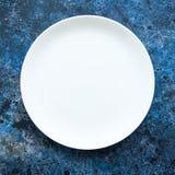 Plat blanc vide rond sur un fond texturisé bleu Vue supérieure Photographie stock