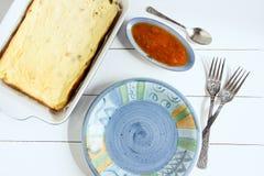 Plat bleu avec la cocotte en terre de fromage blanc de fourchettes sur un fond blanc Vue supérieure, image modifiée la tonalité,  Photographie stock libre de droits