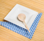 Plat carré vide blanc avec une cuillère en bois Images stock