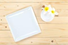Plat carré vide et peu de cuvette avec la fleur sur la table en bois Photographie stock
