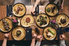 Plat-configuration des mains humaines mangeant des repas et célébrant des vacances image libre de droits