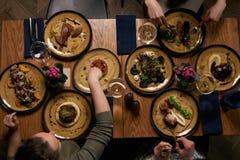 Plat-configuration des mains humaines mangeant des repas et célébrant des vacances photo stock