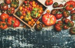Plat - configuration des tomates mûres colorées fraîches au-dessus du fond rustique Image stock