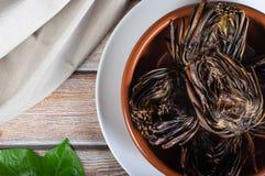 Plat d'artichaut Baked a rôti des artichauts servis dans la cocotte en terre rustique d'argile Vegan et nourriture saine Nourritu photographie stock libre de droits