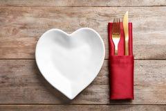 Plat dans la forme de l'ensemble de coeur et de couverts Photographie stock libre de droits