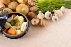 Plat de cocotte en terre avec les légumes et les herbes organiques d'hiver sur le plan de travail de cuisine, l'espace de copie Photo libre de droits