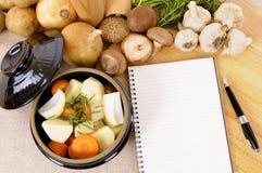 Plat de cocotte en terre avec les légumes et les herbes organiques sur le plan de travail de cuisine avec le livre de cuisine ou  Photographie stock libre de droits